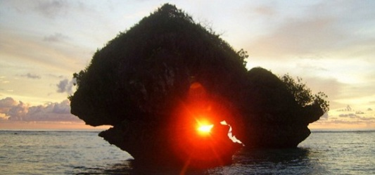 Sunrise through the rock in a tropical island Guam by Lama Tantrapa